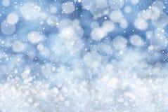 Blauer Weihnachtshintergrund mit Schnee, Snwoflakes und Bokeh Stockfotos