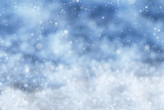 Blauer Weihnachtshintergrund mit Schneeflocken und Schnee Stockfotos