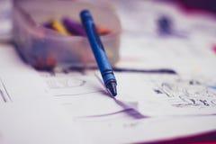 Blauer Zeichenstift und Kinderskizzierende Auflage Stockfoto