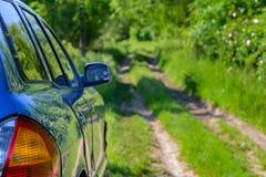 Blaues Auto im Wald Stockfotografie