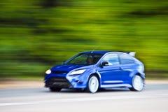 Blaues Autoauf Landstraße schnell fahren Stockbild
