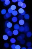 Blaues Blau der Girlande aus Fokus bokeh dunkler Nachtbeleuchtung heraus ist- interessante undeutliche Kreise Stockfoto