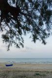 Blaues Boot auf dem Sand nahe dem Meer in Thailand Stockfotografie