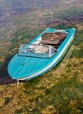 Blaues Boot gebunden oben im flachen Meer Lizenzfreies Stockfoto