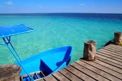 Blaues Boot im hölzernen tropischen Pier in Karibischen Meeren lizenzfreie stockfotos