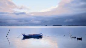 Blaues Boot mit dem Sonnenlicht zwischen den Wolken stockfoto