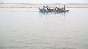 Blaues Boot voll von den Leuten, die durch Fluss der Ganges in Varanasi segeln stock footage