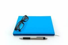 Blaues Buch mit Gläsern und Stift Stockfotos