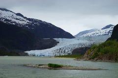 Blaues Eis von Mendenhall-Gletscher mit Schnee bedeckte Berge auf dem Hintergrund und einer kleinen Insel auf dem Vordergrund Stockfotografie