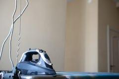 Blaues Eisen auf einem Bügelbrett lizenzfreie stockfotografie