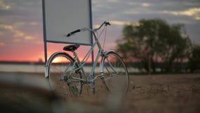 Blaues Fahrrad bleibt am Schild auf einem Strand im Sommersonnenuntergang Pan horizontal stock video