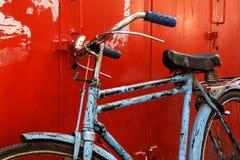 Blaues Fahrrad der Weinlese auf dem roten Hintergrund Stockfoto