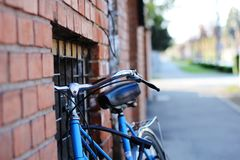 Blaues Fahrrad der Weinlese nahe einer Backsteinmauer Stockbilder