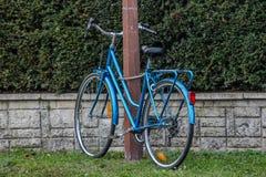 Blaues Fahrrad gegen einen Pfosten, Frankreich Lizenzfreies Stockfoto