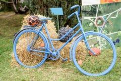 Blaues Fahrrad mit Heu- und pumkpinsdekoration lizenzfreie stockbilder