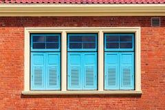 Blaues Fenster auf Backsteinmauer Lizenzfreie Stockbilder