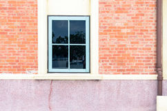 Blaues Fenster auf Backsteinmauer mit überschüssiger Knolle Lizenzfreie Stockfotografie