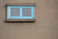 Blaues Fenster auf Backsteinmauer mit grauer Farbe Stockbilder