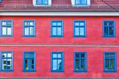 Blaues Fenster auf einem roten Haus Stockfotografie