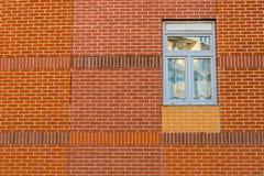 Blaues Fenster auf einer Wand des roten Backsteins Lizenzfreie Stockfotos