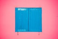 Blaues Fenster auf rosa Wand Stockbild