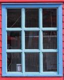 Blaues Fenster auf roter Wand Lizenzfreies Stockfoto