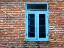 Blaues Fenster und alte Backsteinmauer Stockbilder