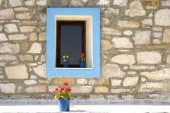 Blaues Fensterfeld mit Blumen Stockfoto