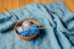 Blaues Garn in wenigem Korb mit Nadeln und Häkelarbeit Lizenzfreies Stockbild