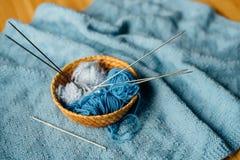 Blaues Garn in wenigem Korb mit Nadeln und Häkelarbeit Lizenzfreie Stockfotos
