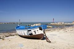 Blaues gebranntes Boot des kleinen Fischens auf der Küste lizenzfreie stockfotografie