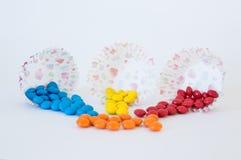 Blaues, gelbes und rotes rundes Süßigkeitsdragée goss aus Papierkörben heraus stockfoto