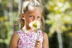 Blaues gemustertes Mädchen, das hinter Blume sich versteckt. Lizenzfreie Stockbilder