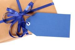 Blaues Geschenktag oder -aufkleber auf Paket des braunen Papiers oder Paket, Draufsicht, Abschluss oben Lizenzfreie Stockbilder