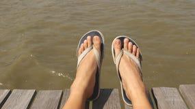Blaues Gewebe Flip Flops auf hölzernem Dock stockfotografie