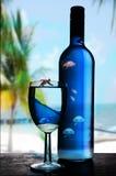 Blaues Glas und Flasche Wein Stockbild