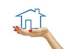 Blaues Haus in der Frauenhand lokalisiert auf Weiß Stockfotografie
