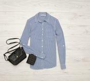 Blaues Hemd in den kleinen Zellen, schwarze Handtasche, Geldbeutel Art und Weisekonzept Ansicht von oben Lizenzfreies Stockfoto