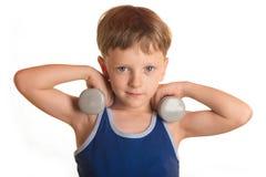 Blaues Hemd des Jungen, das Übungen mit Dummköpfen über weißem backgro tut Stockfoto