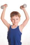 Blaues Hemd des Jungen, das Übungen mit Dummköpfen über weißem backgro tut Lizenzfreie Stockfotografie