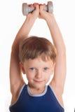 Blaues Hemd des Jungen, das Übungen mit Dummköpfen über weißem backgro tut Lizenzfreie Stockfotos