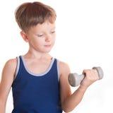 Blaues Hemd des Jungen, das Übungen mit Dummköpfen über weißem backgro tut Lizenzfreies Stockbild