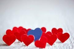 Blaues Herz und viele roten Herzen auf dem weißen Hintergrund valentin Stockbild