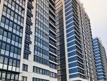 Blaues hohes modernes monolithisches Rahmengebäude, Haus, Neubau, ein Wolkenkratzer mit widergespiegelten Fenstern gegen einen bl stockfoto