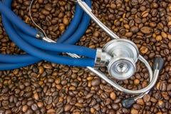Blaues Kardiologiestethoskop, das auf der Draufsicht des Bohnenkaffees liegt Effekte des Kaffees und des Koffeins auf Herz-Kreisl stockbilder