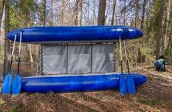 Blaues Katamaran mit vier Rudern nähern sich Bäumen im Wald stockfotografie