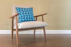 Blaues Kissen auf Holzstuhl mit grüner Wand lizenzfreie stockfotos