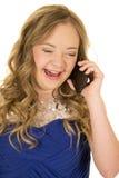 Blaues Kleid des Mädchens, das am Telefon lacht Lizenzfreies Stockbild