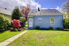 Blaues kleines Haus mit Frühlingslandschaft vom Hinterhof. Stockbilder