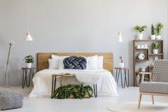 Blaues Knotenkissen auf weißem hölzernem Bett in graues Schlafzimmer Innenwi stockfotos